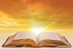Open bible. Old antique bible as an open book with sunlight bursting from the pages Royalty Free Stock Images