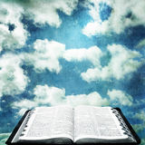 Open Bible with Grunge Sky. Open Bible over cloudy sky with grunge effects Stock Photos