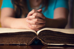 Open Bible With Praying Girl. Girl praying with hands on 150 year old Bible Royalty Free Stock Images