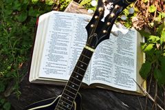 Open Bible with propped up mandolin and the sun shining on it. Royalty Free Stock Photos
