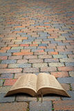 Open bible roadway. Photo of  an open bible resting on paved roadway ideal for own text etc Royalty Free Stock Photo