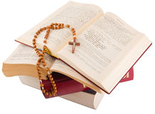 Open Bible and rosary. Open Holy Bible lying on stack of old books with glasses, cross and beads Royalty Free Stock Images