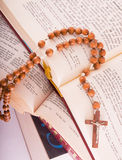 Open Bible and rosary. Open Holy Bible lying on stack of old books with glasses, cross and beads Stock Photography