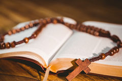 Open bible with rosary beads. On wooden table stock photography