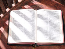 Open Bible Sitting on Old Wooden Sunlit Chair Stock Photo