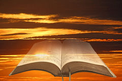 Open bible sky background. Photo of open holy bible set against a fire-red sky with storm clouds ideal for own text etc Royalty Free Stock Photos