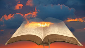 Open bible sky background. Photo of open holy bible set against a fire-red sky with storm clouds ideal for own text etc Stock Images