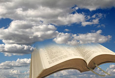 Open bible sky clouds background. Photo of a modern bible with open pages against a sky clouds background ideal for own text etc Stock Photo
