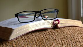 Open bible with spectacles or reading glasses on top of it.