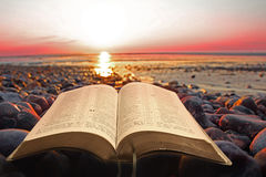 Open bible spiritual light on seashore. Photo of open bible resting on beach pebble at sunset  depicting spiritual light Stock Photos