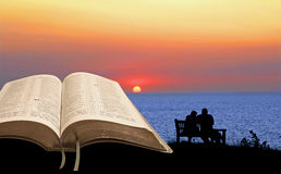 Open bible spiritual tranquility. Photo of  an open bible with sunset and silhouetted couple sitting on bench ideal for spiritual tranquility peace etc Stock Photography