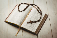 Open bible and wooden rosary beads Stock Photos