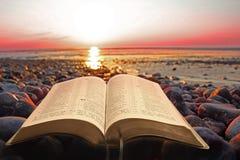 Open bijbel geestelijk licht op kust Stock Foto's