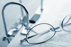 Open binder and glasses over document Royalty Free Stock Photo