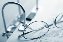 Open bindmiddel en glazen over document Royalty-vrije Stock Foto