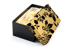 Open Black and Gold Gift Box. Black and gold cardboard gift box, opened and showing tissue paper inside stock image