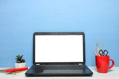 Open black laptop. On table on blue background. Concept workplace stock photos