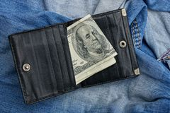 Open black leather wallet rests on blue trousers. Part of blue pants with a pocket and a black open purse with bills Royalty Free Stock Images