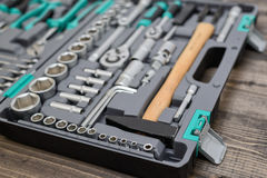 Open black toolbox with different instruments on wooden surface Stock Images