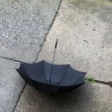 Open black umbrella resting on concrete surface Royalty Free Stock Photography
