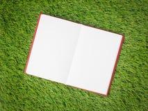 Open blank book on artificial green grass Royalty Free Stock Photos