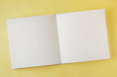 Open blank book on yellow background. Opened blank book Stock Photo