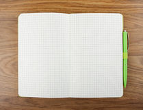 Open blank checked notebook with green pen on a table. Royalty Free Stock Photos