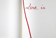 Open blank exercise book (love is). Open blank exercise book with red bookmark (love is Royalty Free Stock Image