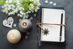 Open blank journal with blossom. And lit candles on grey concrete background. Flat lay top view style Stock Photo