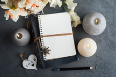 Open blank journal with blossom. And lit candles on grey concrete background. Flat lay top view style royalty free stock images