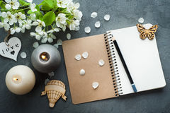 Open blank journal with blossom. And lit candles on grey concrete background. Flat lay top view style royalty free stock photos