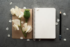 Open blank journal with flowers. On grey concrete background. Flat lay top view style Stock Photos