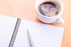Open blank note book with coffee cup on table. Open blank note book with coffee cup and a pen on wood table Stock Image