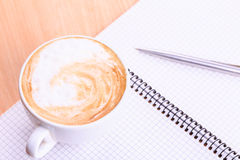 Open blank note book with coffee cup on table. Open blank note book with coffee cup and a pen on wood table Royalty Free Stock Photography