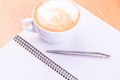 Open blank note book with coffee cup on table. Open blank note book with coffee cup and a pen on wood table Stock Photos