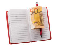 Open blank notebook with ballpoint pen and rolled euro banknote Royalty Free Stock Photo