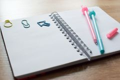An open blank notebook with a blue and pink rabbit-shaped pen and funny kawaii clips royalty free stock photos