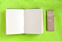 Open blank notebook and crayons on green background Stock Images