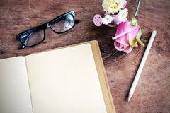 Open blank notebook with flower and glasses on wooden table Stock Photo