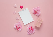 Open blank notebook with gift box, orchid flowers and hearts on Royalty Free Stock Photography