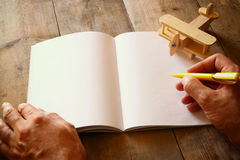 Open blank notebook and man hands next to toy aeroplane on wooden table. retro style filtered image Stock Photo