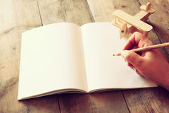 Open blank notebook and man hands next to toy aeroplane on wooden table. retro style filtered image Stock Photography