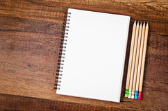 Open blank notebook with many wooden pencils. Royalty Free Stock Photo