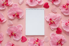 Open blank notebook with orchid flowers and hearts on a pink bac Royalty Free Stock Image