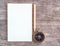 Open blank notebook with pencil and compass over a wooden backgr Royalty Free Stock Photography