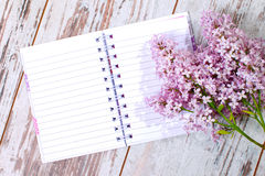 Open blank notebook ready to write ... The beautiful lilac on a wooden surface stock photography