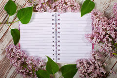 Open blank notebook ready to write ... The beautiful lilac on a wooden surface stock photo