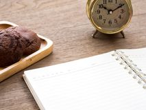 The open blank notebook side of the cookie and there is a golden clock in the side on the wooden table.  Royalty Free Stock Images
