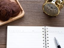The open blank notebook side of the cookie and there is a golden clock in the side on the wooden table Royalty Free Stock Images