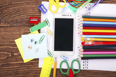 Open blank notebook, white smartphone with frame of school suppl Royalty Free Stock Images